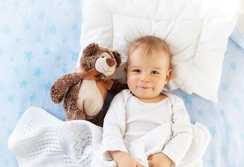 cute baby boy lying on the bed with teddy bear