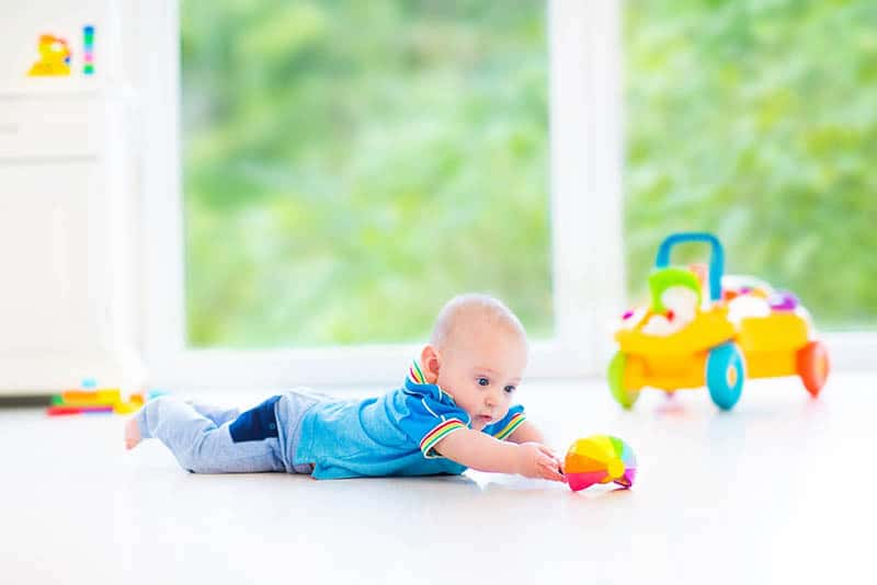 cute baby boy lying on tummy on the floor and playing with toy