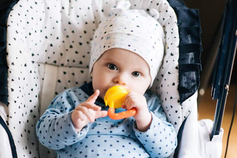 cute baby boy wearing matching outfit and holding a teether in hand