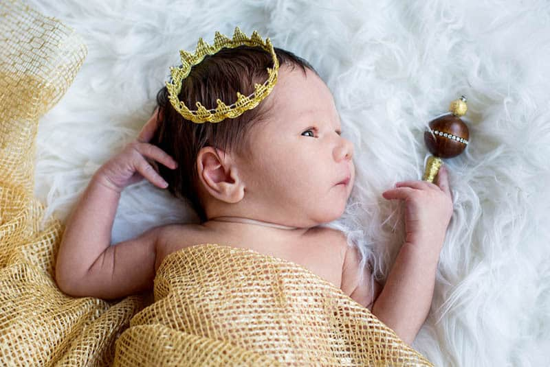 cute baby boy with golden crown lying in bed