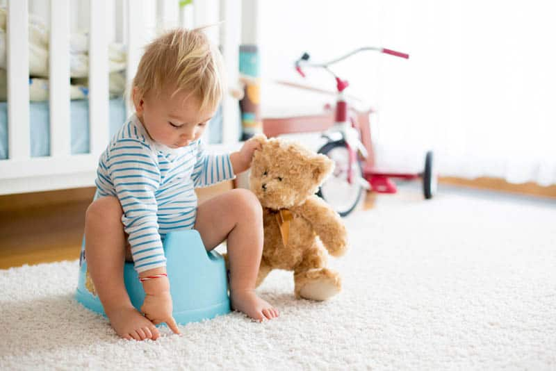 cute baby toddler on a potty train playing with his teddy bear