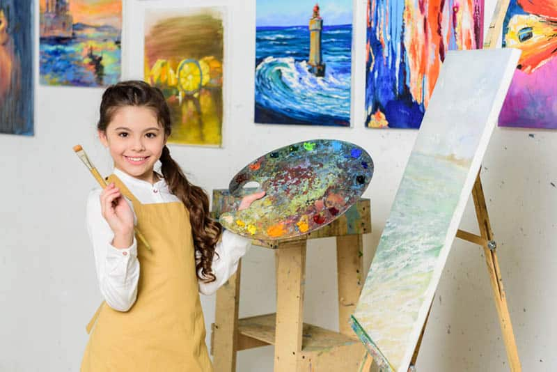 cute girl posing with painting brush and canva