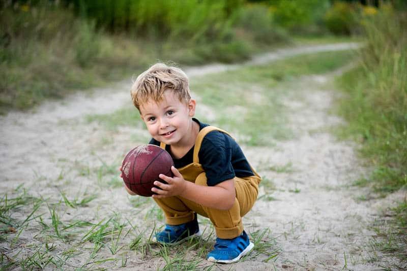 cute little boy holding a ball on the sand