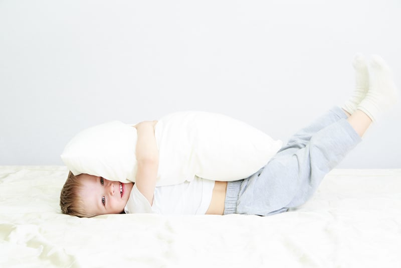 cute little boy hugging big white pillow on the bed