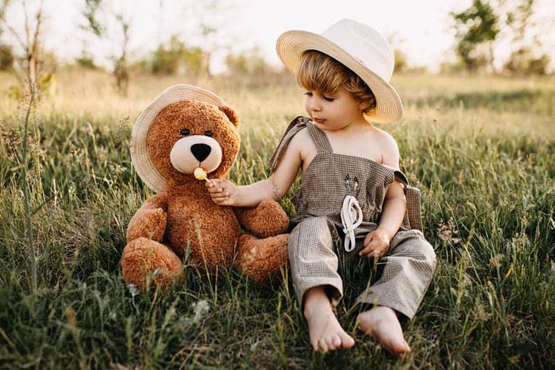 cute little boy sitting on grass with teddy bear