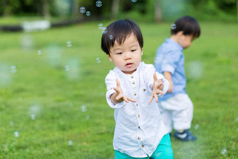 cute little boys playing with bubbles outdoor