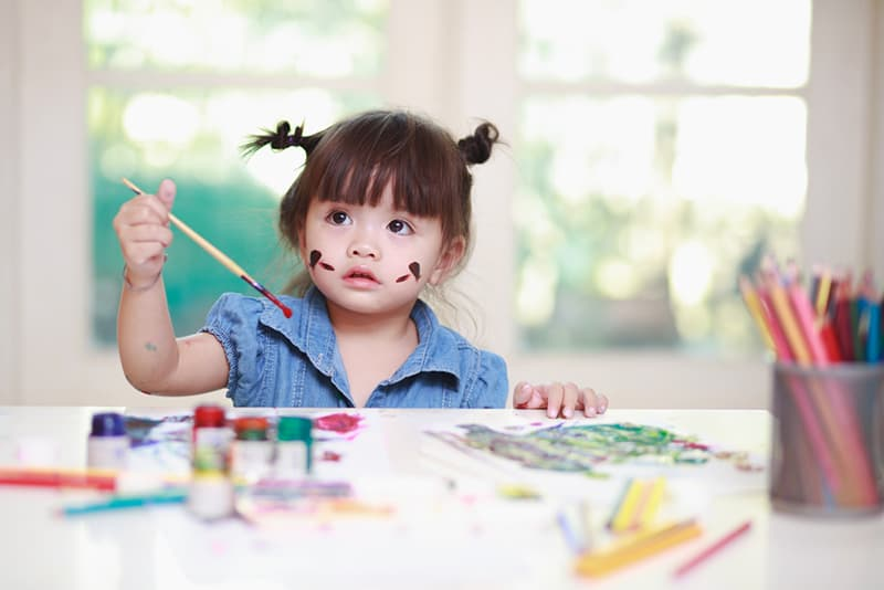 cute little girl holding a paint brush and sitting by the table