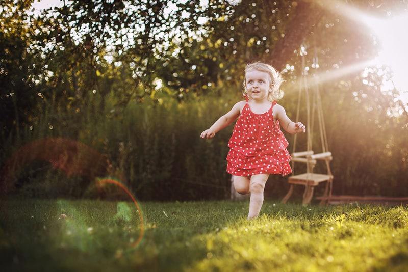 cute little girl in a red dress running in sunlight on the grass