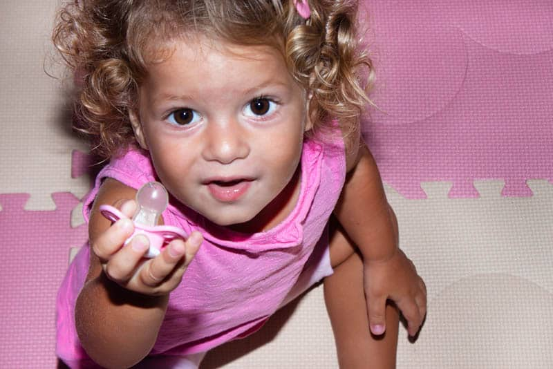 cute little girl in pink clothes giving a pacifier up