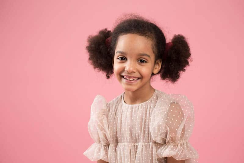 cute little girl posing in front of pink background