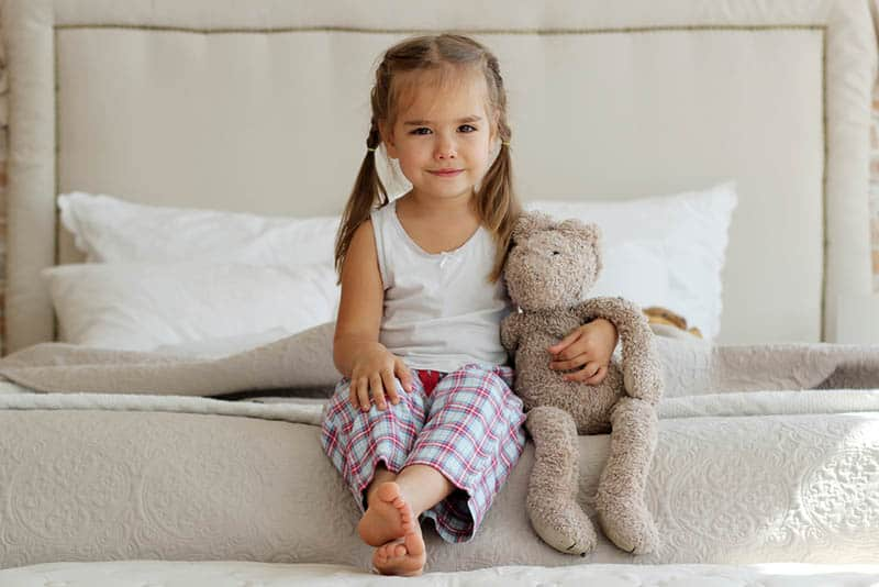 cute little girl sitting on the bed with her teddy bear toy