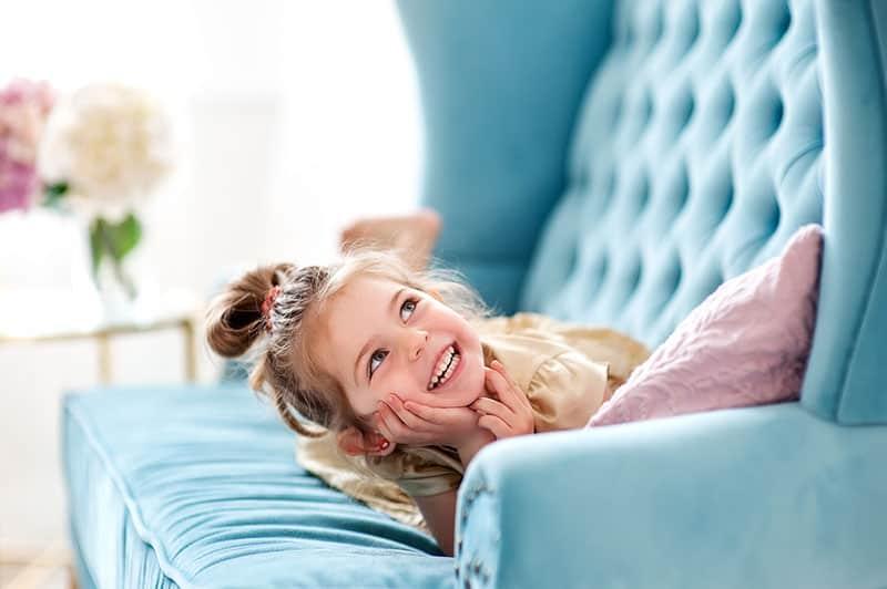 cute little girl smiling on sofa