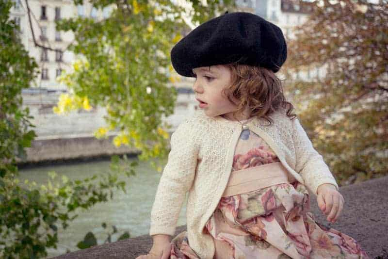 cute little girl with french hat sitting outdoor