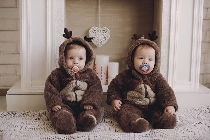 cute twin babies sitting on the floor in deer costumes