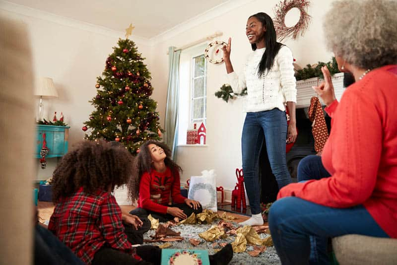 family playing charades at home on christmas
