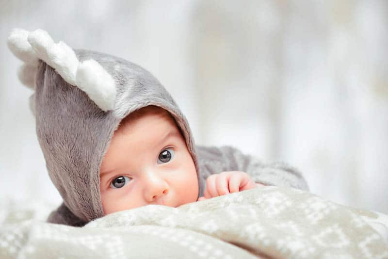 funny baby boy wearing baby costume while lying on the belly