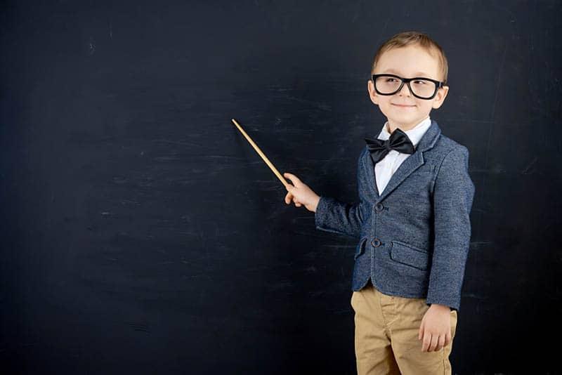 funny little boy standing against blackboard
