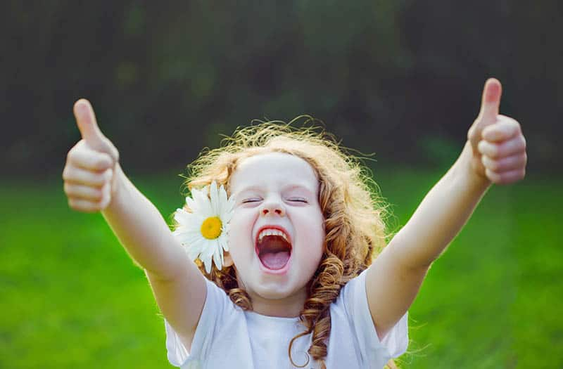 laughing little girl with daisy in her hair