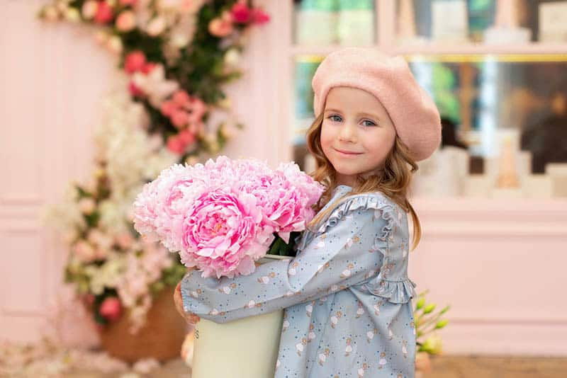 little girl with curly hair and in a beret with bouquet of peonies