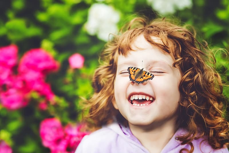 little red hair girl with butterfly on her nose smiling