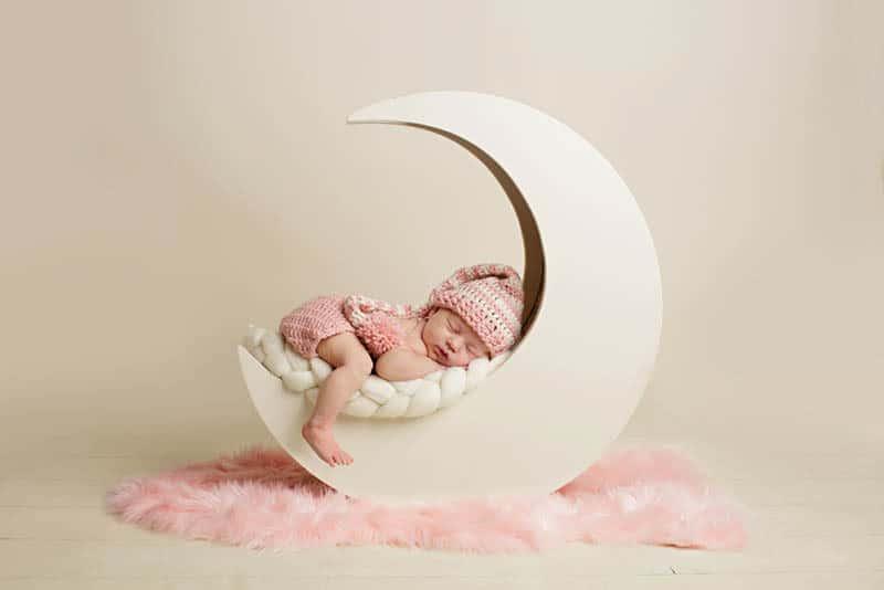 newborn baby girl sleeping while photoshooting in studio