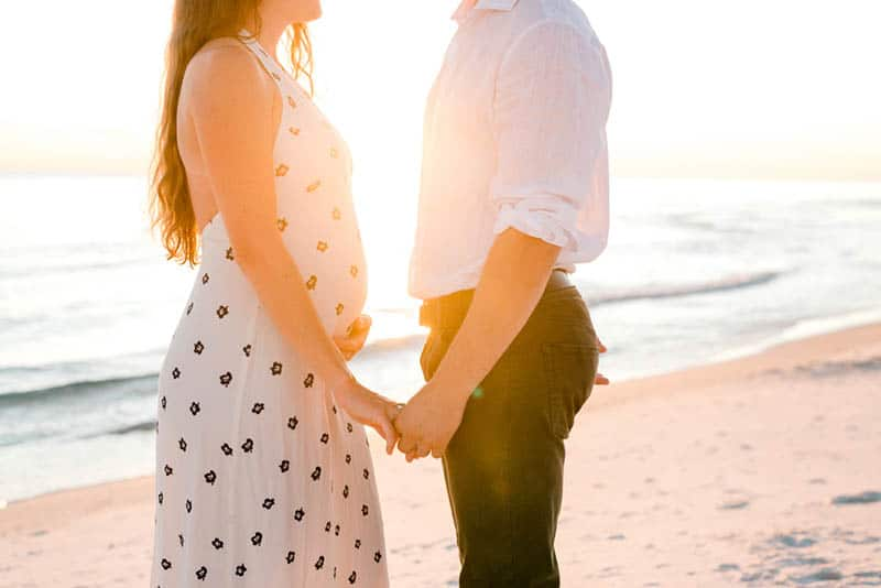 pregnant woman holding hands with her husband on the beach