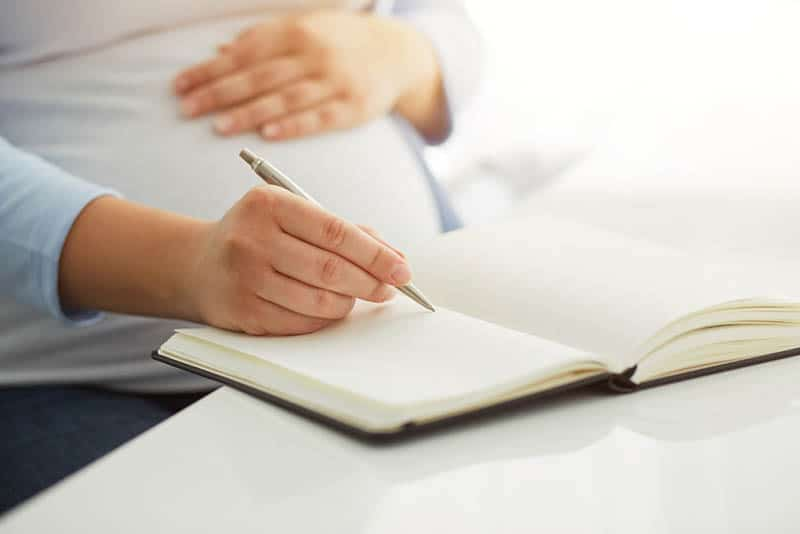pregnant woman writing to her diary on table
