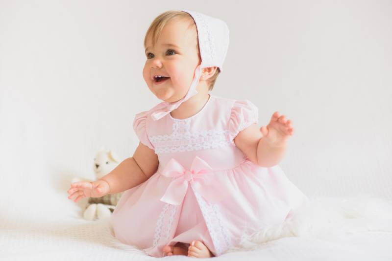 smiling baby girl wearing a dress and hat