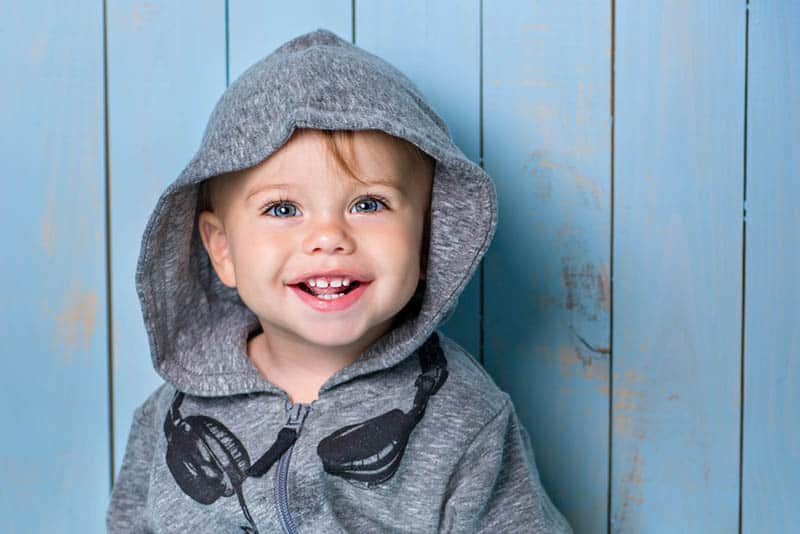 smiling little boy wearing hoodie and standing in front of blue wooden wall