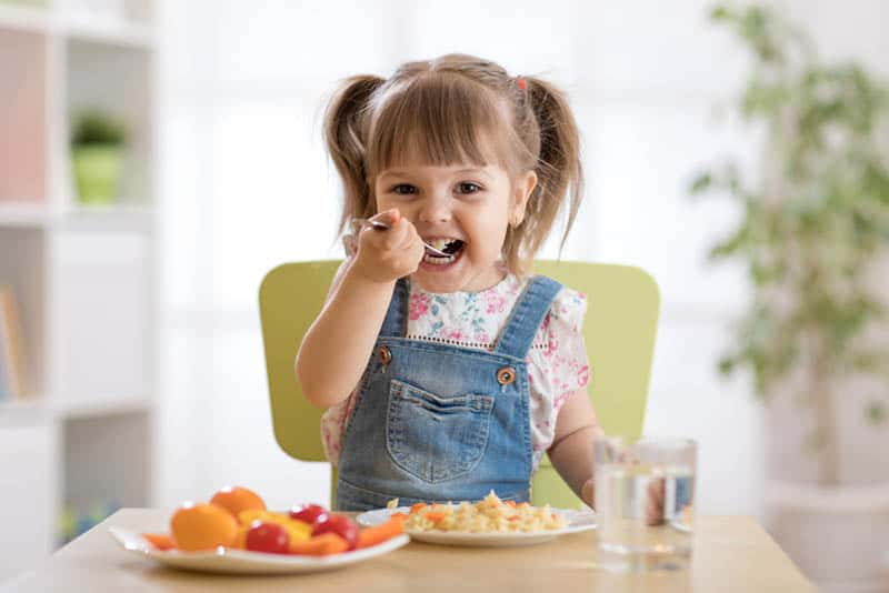 smiling little girl eating lunch