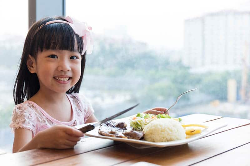 smiling little girl posing with food on the plate