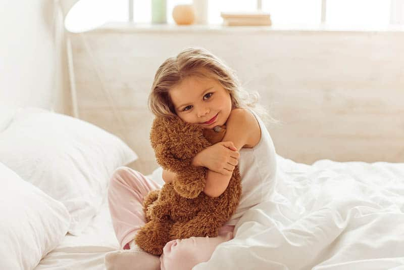 sweet little girl sitting on the bed and hugging a teddy bear