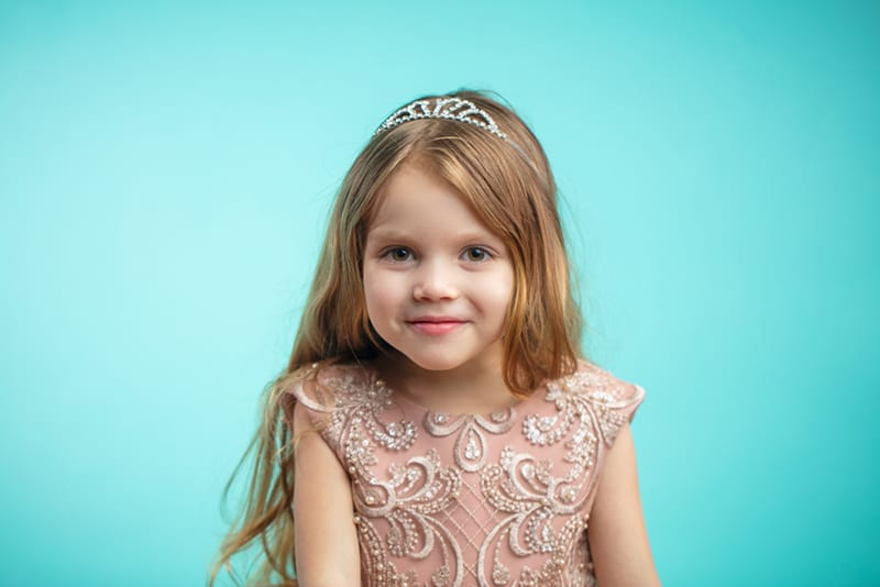 sweet little girl wearing a crown and a princess dress and smiling