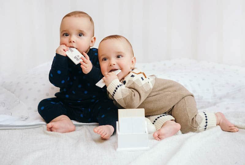 sweet twin babies chewing wooden boards