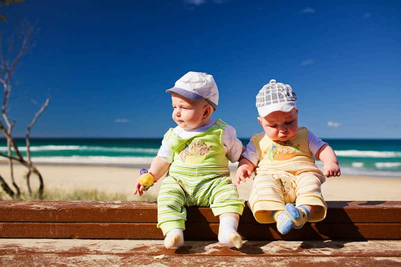 twin babies sitting outdoor on the beach