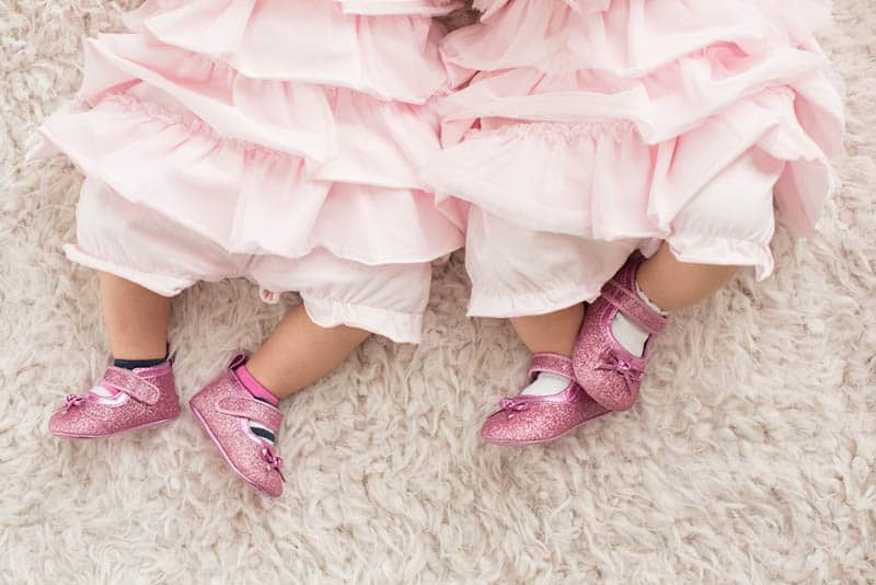 twin babies wearing the same dresses and pink glitter shoes