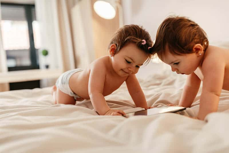 twin baby sisters playing with tablet on the bed