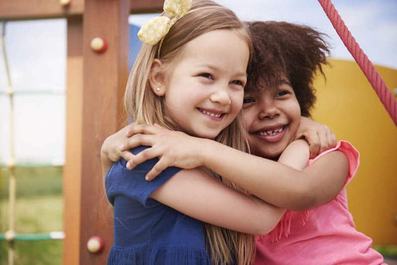 two adorable little girls hugging outdoor