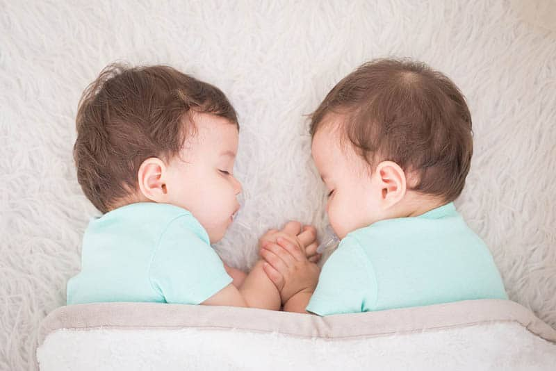 two cute twin babies sleeping together holding hands