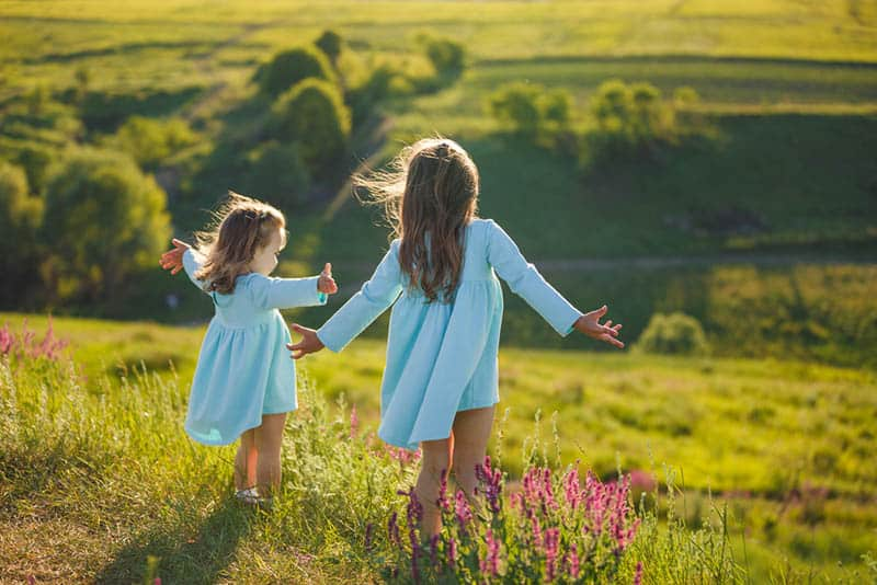 two little girls in dresses spreading arms in nature