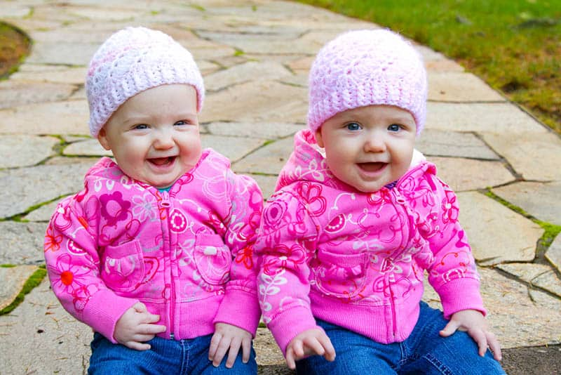 two smiling twin girl babies sitting outdoor