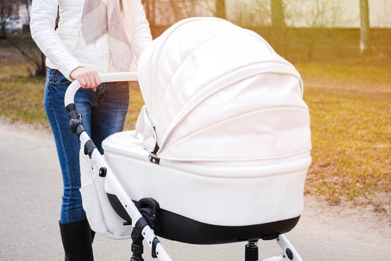 woman pushing baby strollers with white canopy
