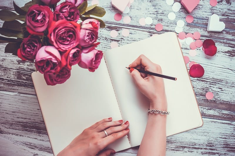 woman writing an anniversary love letter to her husband