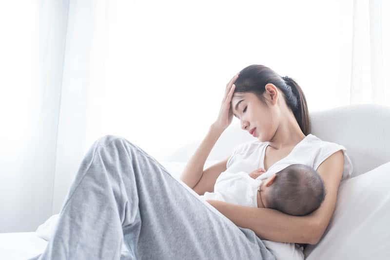 worried woman breastfeedig baby on the bed