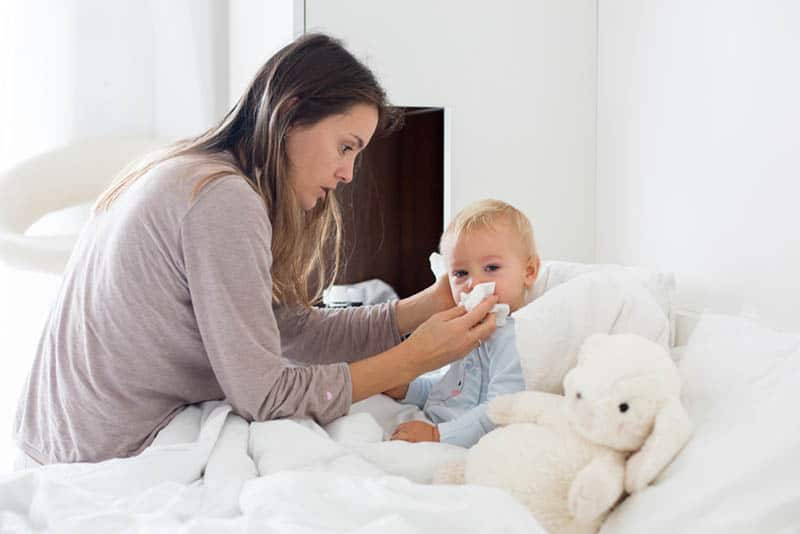 young mother cleaning baby nose in bed