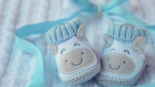 blue knitted baby shoes for a first grandchild announcement