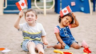 adorable little boy and girl holding canadian flags on the beach