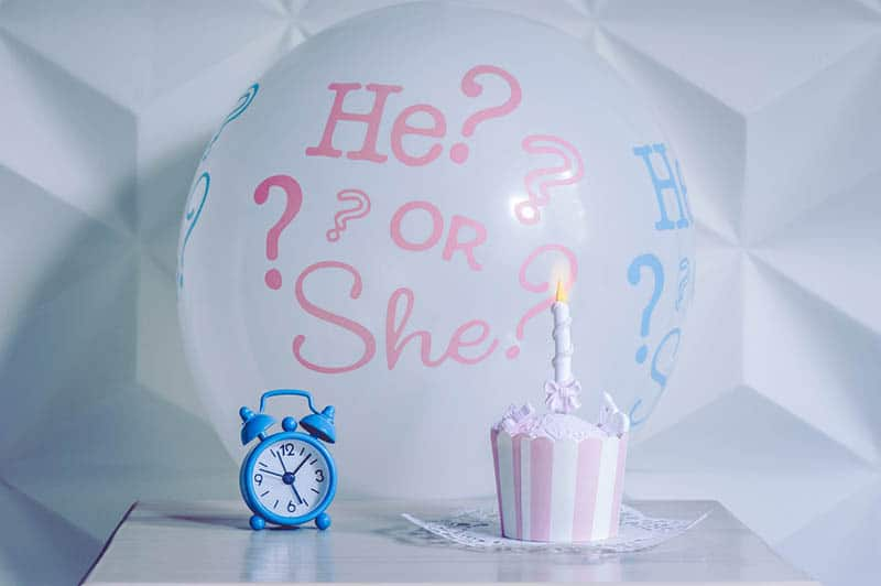 A balloon he or she from a gender reveal party with sweet cake and alarm clock