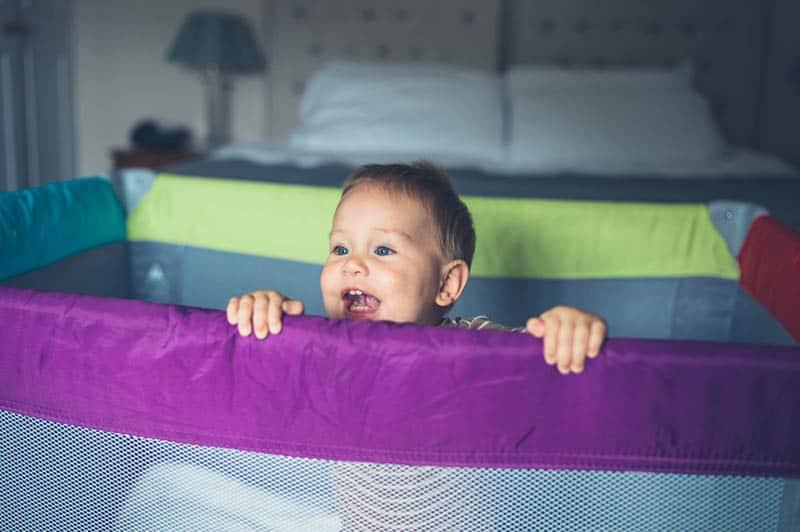 A happy little baby is standing in his playpen