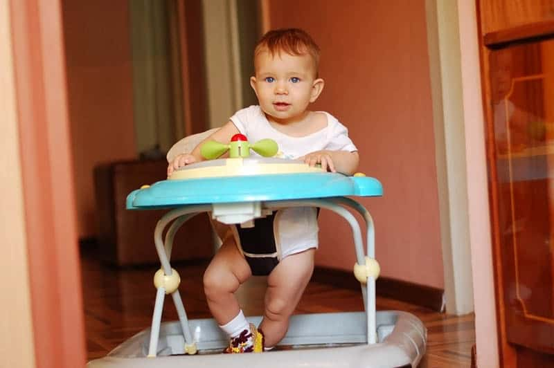 A little boy sits in baby walkers and smile